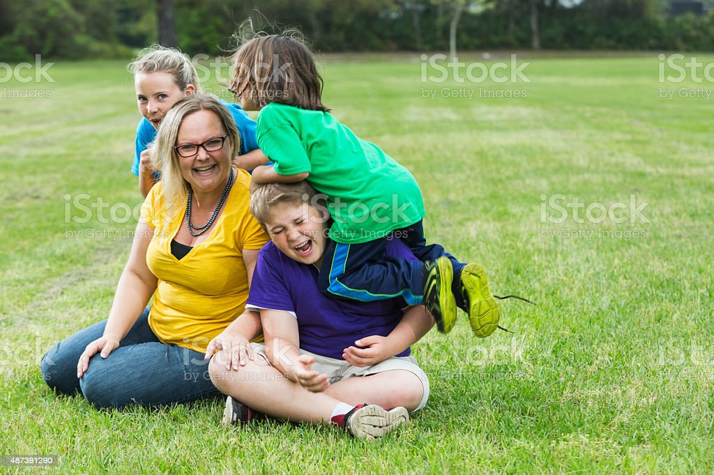 Mother and three children playing in the park stock photo