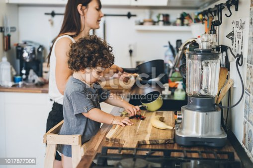 Mother and toddler boy cooking at home in the kitchen
