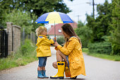 istock Mother and toddler child, boy, playing in the rain 1255003897
