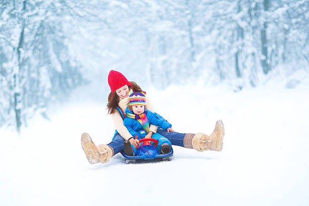 Mother and toddler daughter enjoying sledge ride in snowy park stock photo