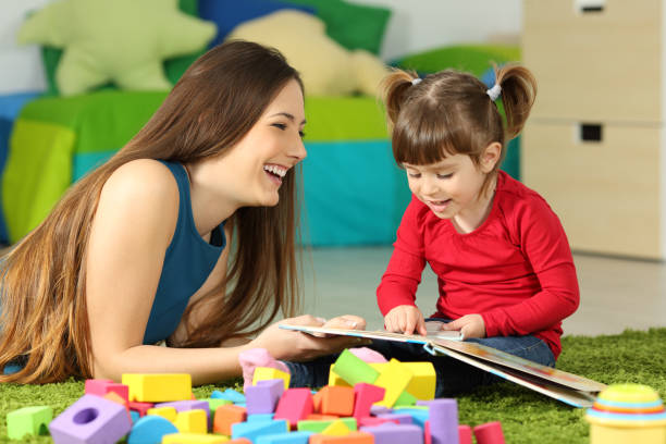 Mother and toddler playing with a book stock photo