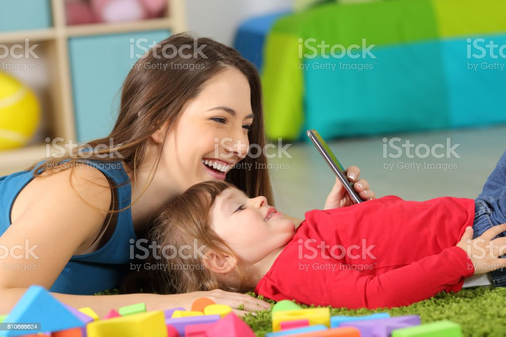 Mother and toddler playing with a smart phone stock photo