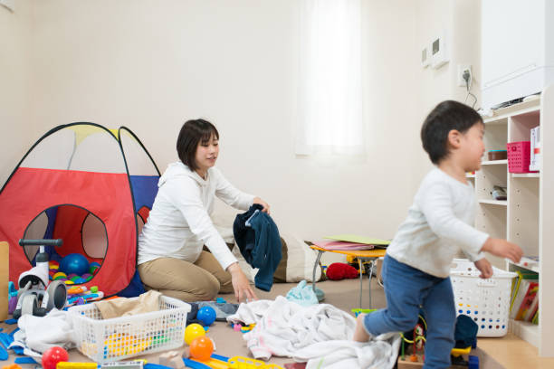 Mother and toddler tidying up room stock photo