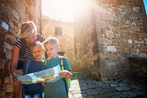 mother and tourist sons checking map in an italian town - italien urlaubsziele stock-fotos und bilder