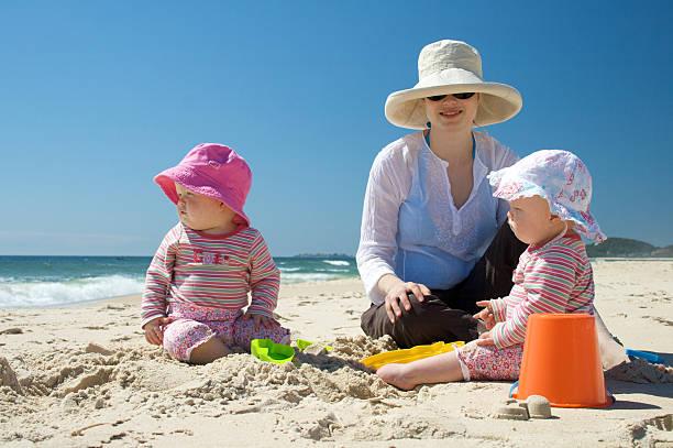mutter und zwei kinder am strand - sonnenbrille kleinkind stock-fotos und bilder