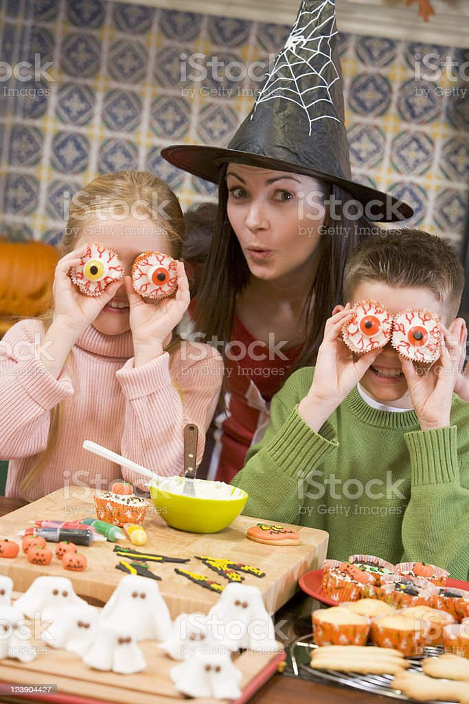 Mother and two children at Halloween playing with treats royalty-free stock photo