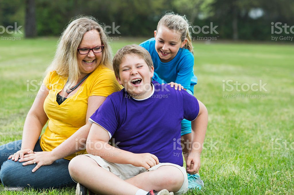 Mother and two children laughing in the park stock photo