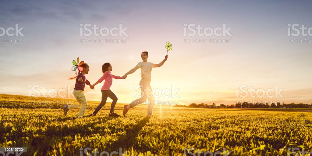 Mutter und zwei Töchter spielen auf der Wiese – Foto