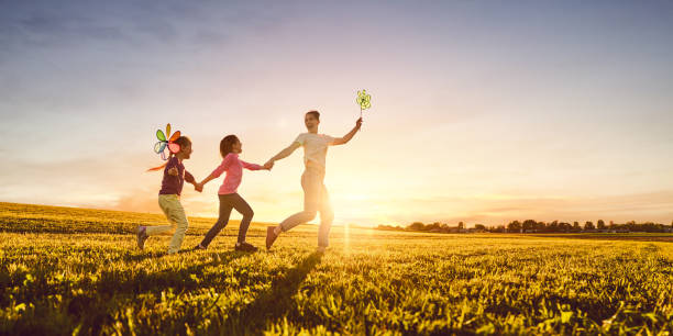 mother and two daughters are playing on meadow stock photo
