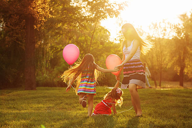 mother and two daughters circling - kinder picknick spiele stock-fotos und bilder