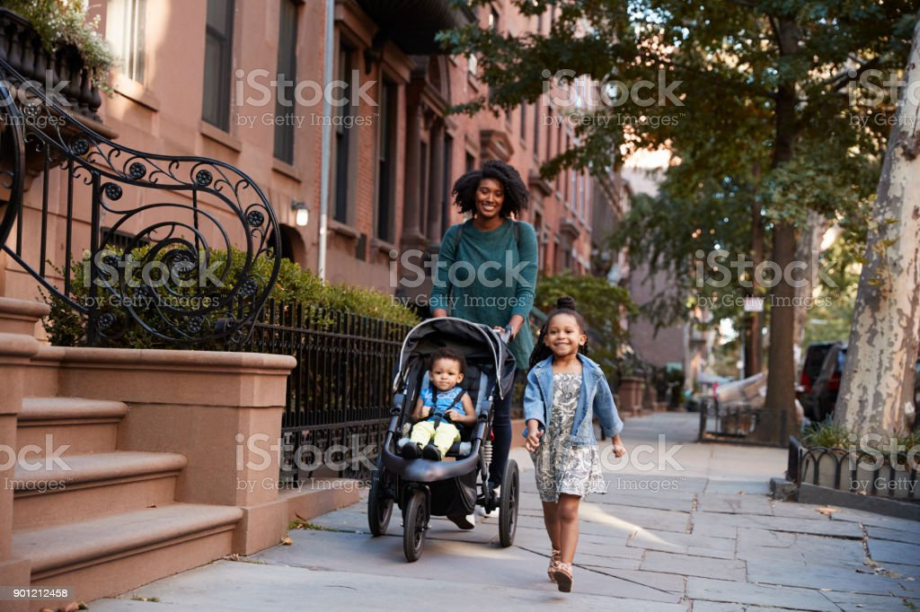 Mother and two daughters taking a walk down the street stock photo
