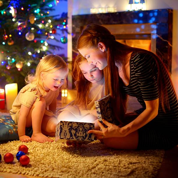 mother and two little daughters opening a magical christmas gift - little girls giving head stock photos and pictures