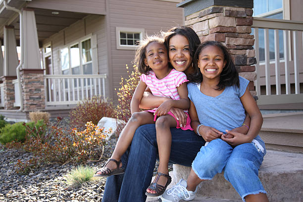 A mother and two little girls smiling on a front porch stock photo