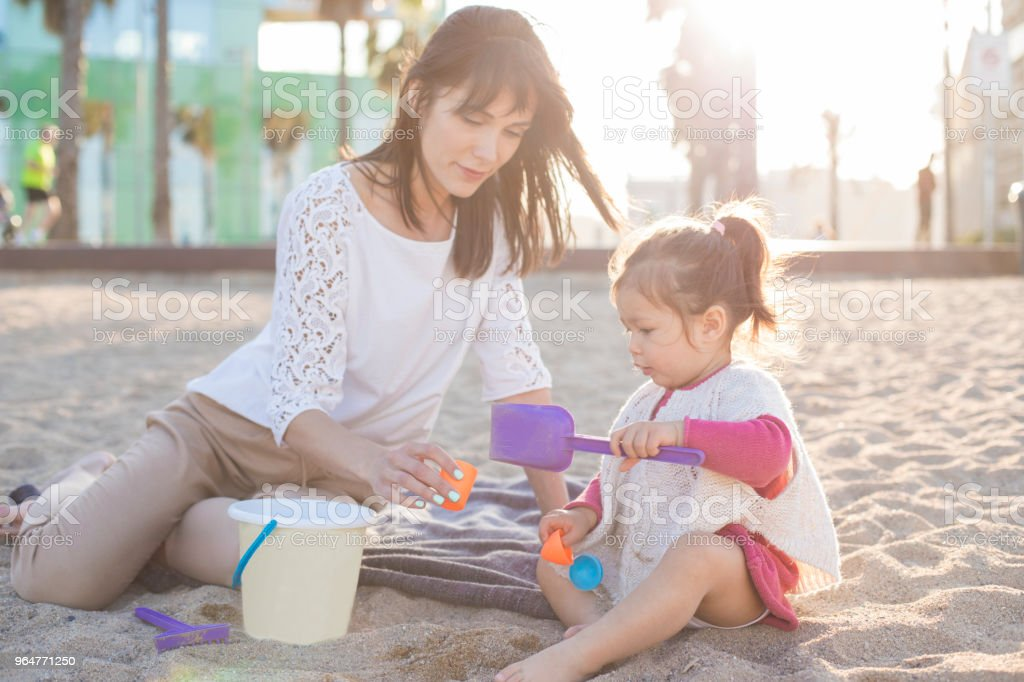 Mother and two year old baby girl playing at the beach royalty-free stock photo