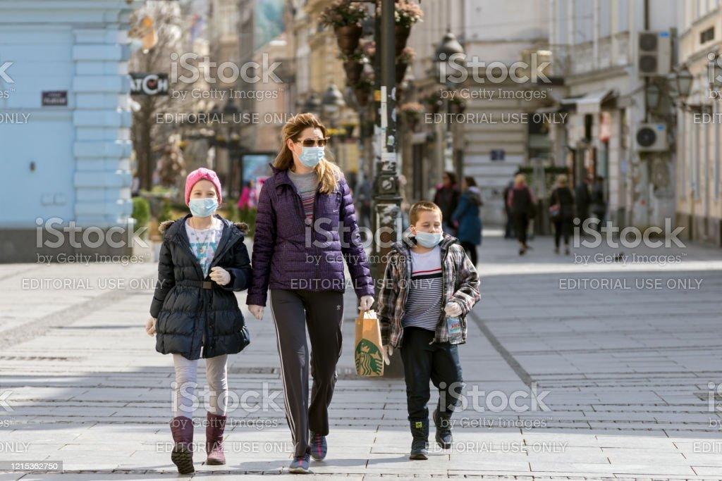 Madre y dos niños pequeños caminando por las calles de la ciudad usando máscaras faciales contra coronavirus. COVID - 19 pandemia. Vista de la calle en el centro de la ciudad - Foto de stock de Adulto libre de derechos