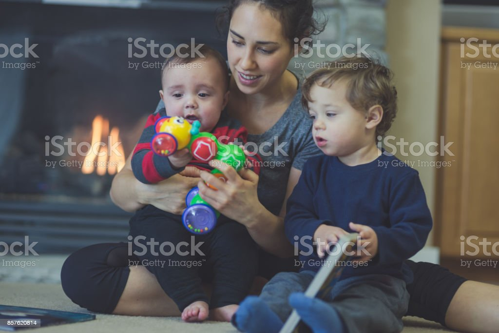 Mother and two young sons play int the living room stock photo