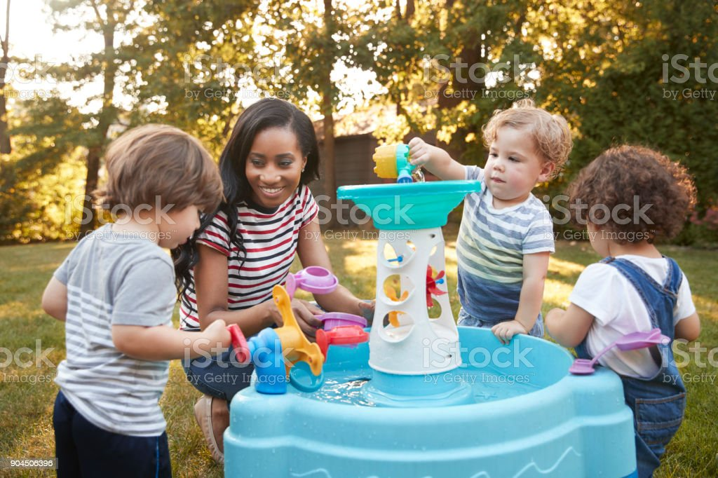 Mother And Young Children Playing With Water Table In Garden stock photo
