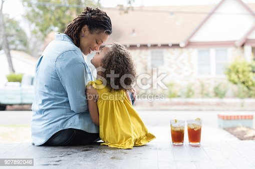 In this view from behind, a mid adult mother and her preschool age daughter sit on their front porch steps and rub noses.  There are two glasses of iced tea beside them.