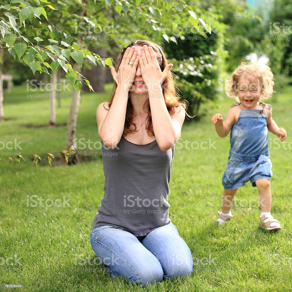 Mother and young daughter playing hide and seek outdoors stock photo