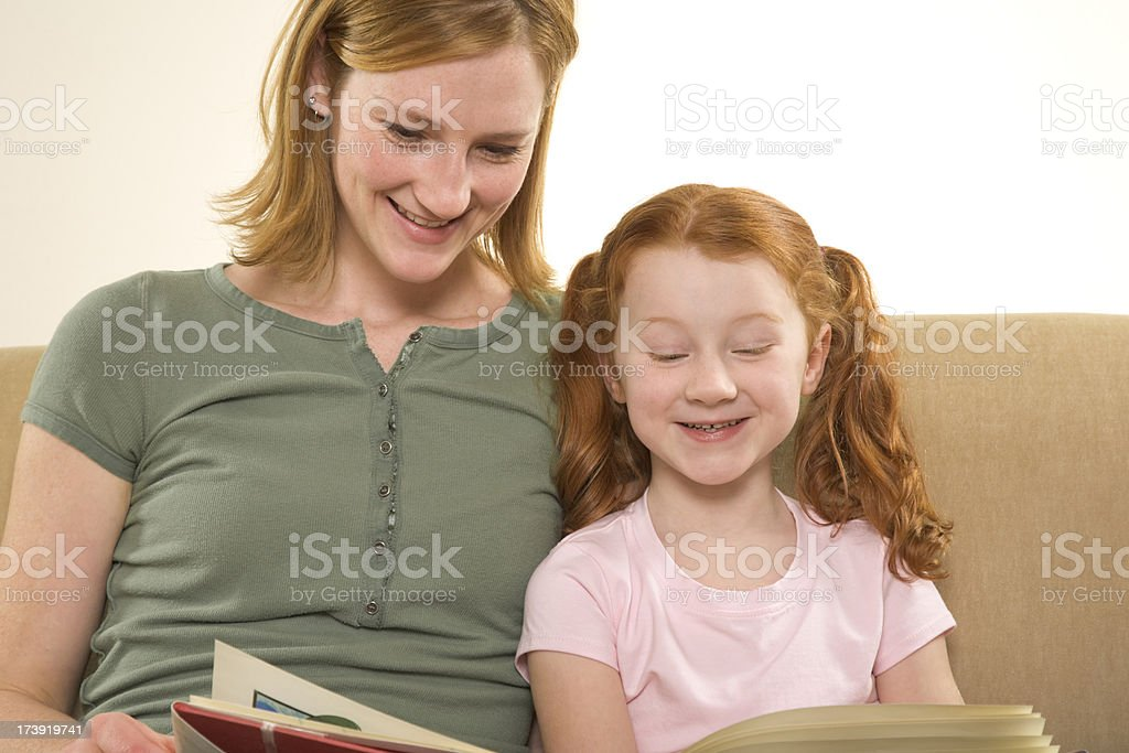 Mother and young daughter sitting on sofa reading storybook stock photo