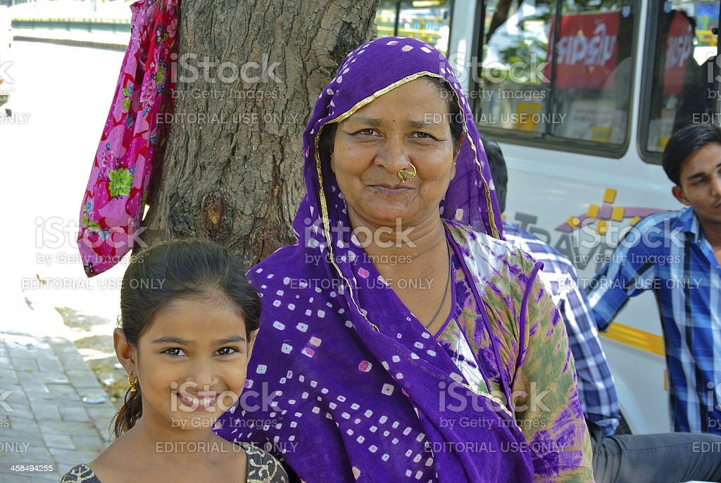 Mother and young daughter sitting under the tree royalty-free stock photo