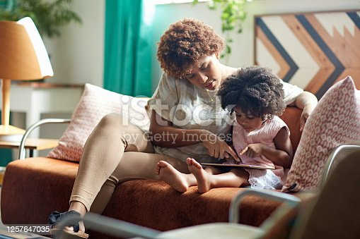 Afro-Caribbean mother sitting on sofa next to preschool aged daughter and showing her how to use digital tablet in family home.