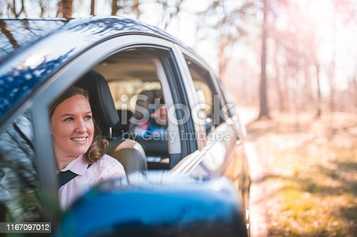 Shot of mother and young boy sitting and driving in a car. Thy are happy and smiling. It is sunny.