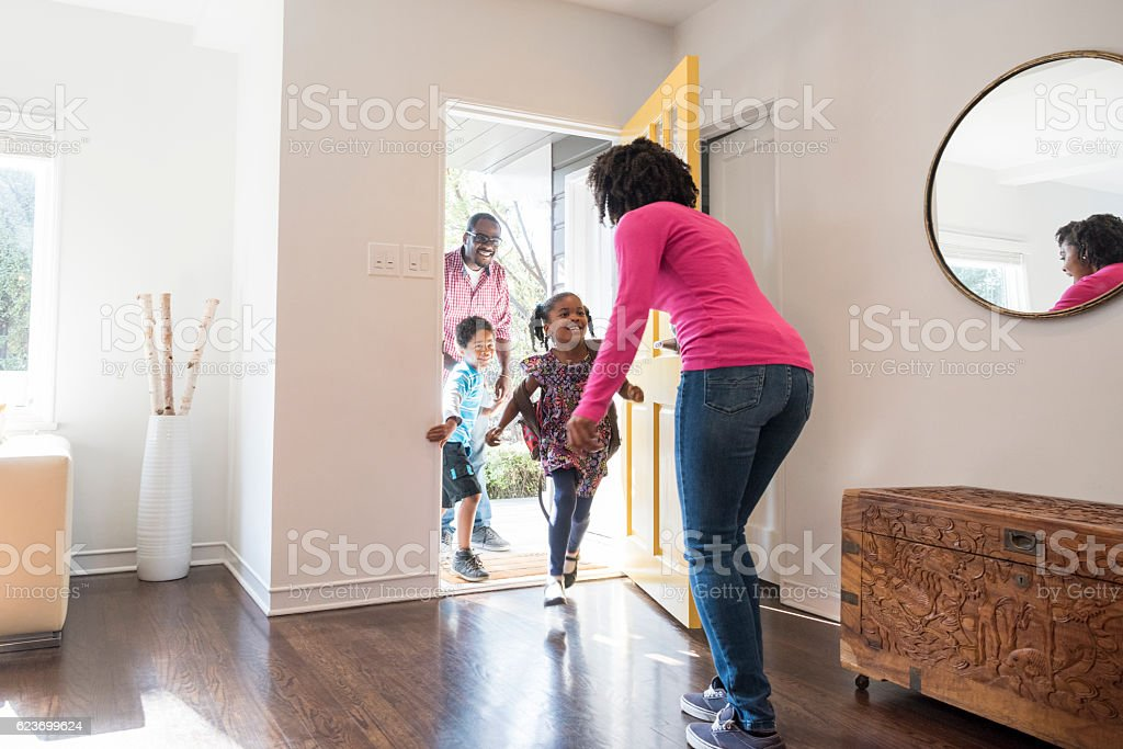 Mother answering the door to her family stock photo