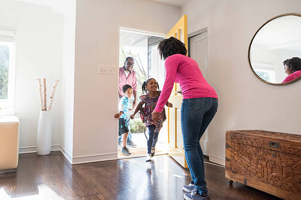 Mother answering the door to her family Two children run into the house and their mother is ready to welcome them entering stock pictures, royalty-free photos & images