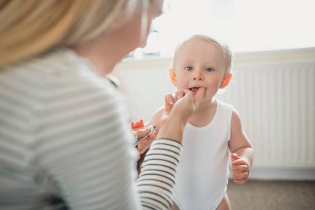 annesi diş çıkarma jeli bebeğim oğlunun ağız için geçerlidir. - baby teeth stok fotoğraflar ve resimler