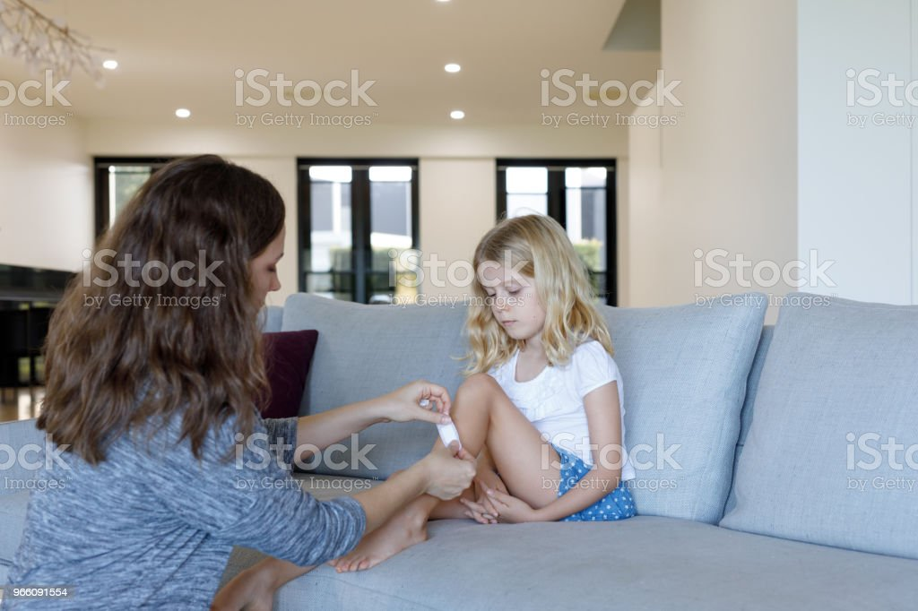 Mother Applying Adhesive Bandage to Daughter - Royalty-free 6-7 Years Stock Photo