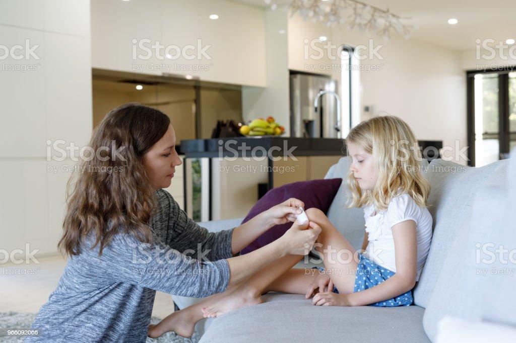 Mor ansöker självhäftande Bandage till dotter - Royaltyfri 6-7 år Bildbanksbilder