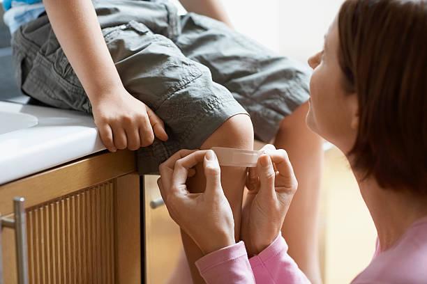 Mère appliquer Bandage à Son fils le genou - Photo