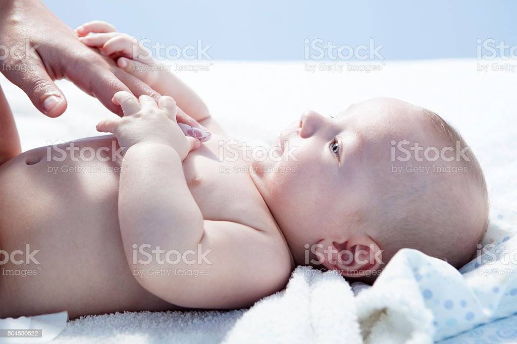 Mother applying cream over baby boy stock photo