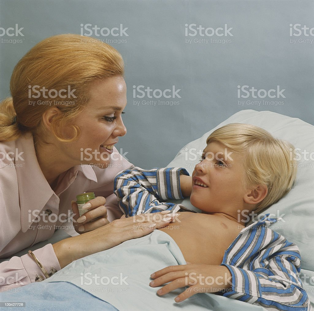 Mother applying ointment on child's chest, smiling royalty-free stock photo