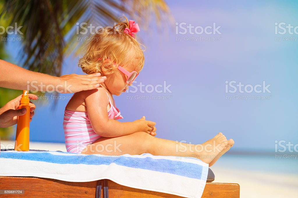 mother applying sunblock cream on daughter shoulder stock photo