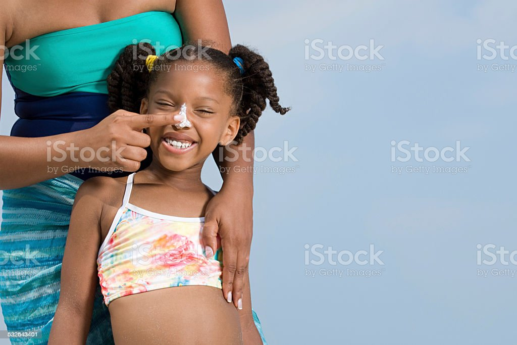 Mother applying suncream to daughters nose stock photo
