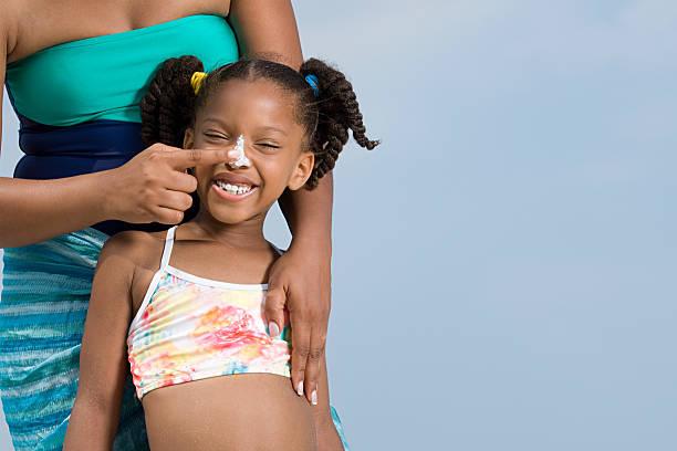 mãe e filhas nariz aplicação de protector solar - filtro solar - fotografias e filmes do acervo