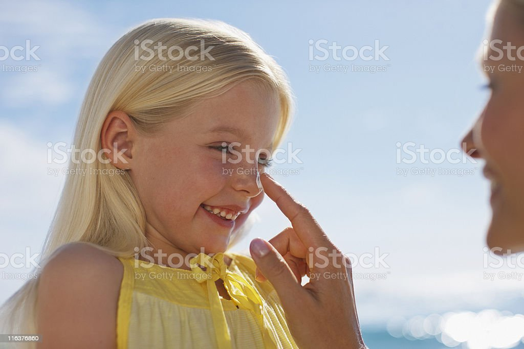 Mother applying sunscreen to daughters nose stock photo
