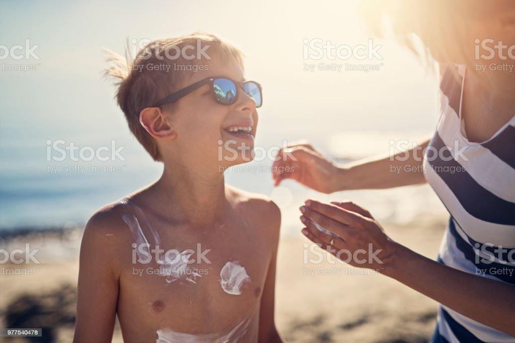 Anwendung von Sonnenschutzmitteln, Sohn Mutter – Foto
