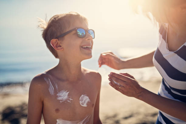 Mother applying sunscreen to son Mother applying sunscreen to son. Sunny summer day on beach. Nikon D850 suntan lotion stock pictures, royalty-free photos & images