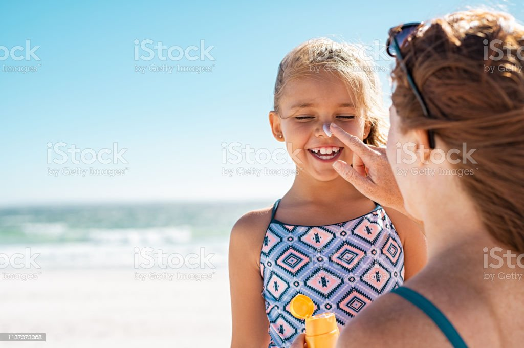 Mother applying suntan lotion on daughter face Young mother applying protective sunscreen on daughter nose at beach. Woman hand putting sun lotion on child face. Cute little girl with sunblock at seaside with copy space. 8-9 Years Stock Photo