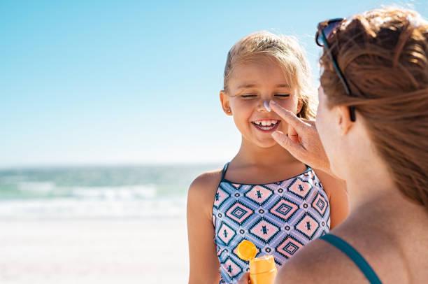 madre che applica la lozione abbronzante sul viso della figlia - protezione foto e immagini stock