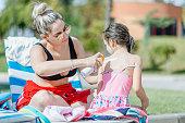 istock Mother applying suntan lotion on daughter shoulder 1197529168