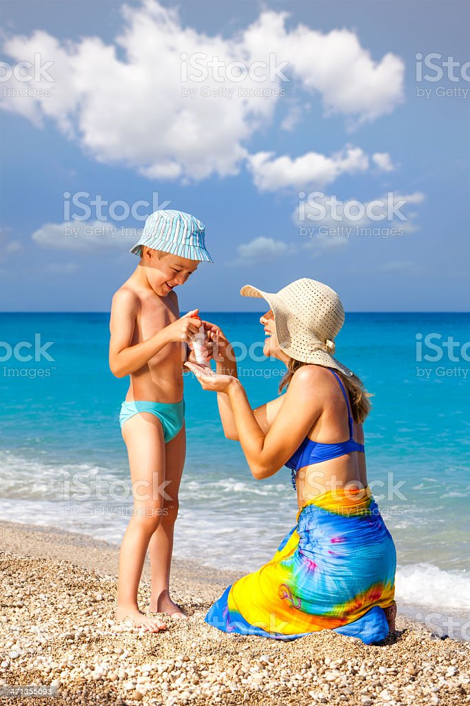 Mother Applying Suntan Lotion To Her Son royalty-free stock photo