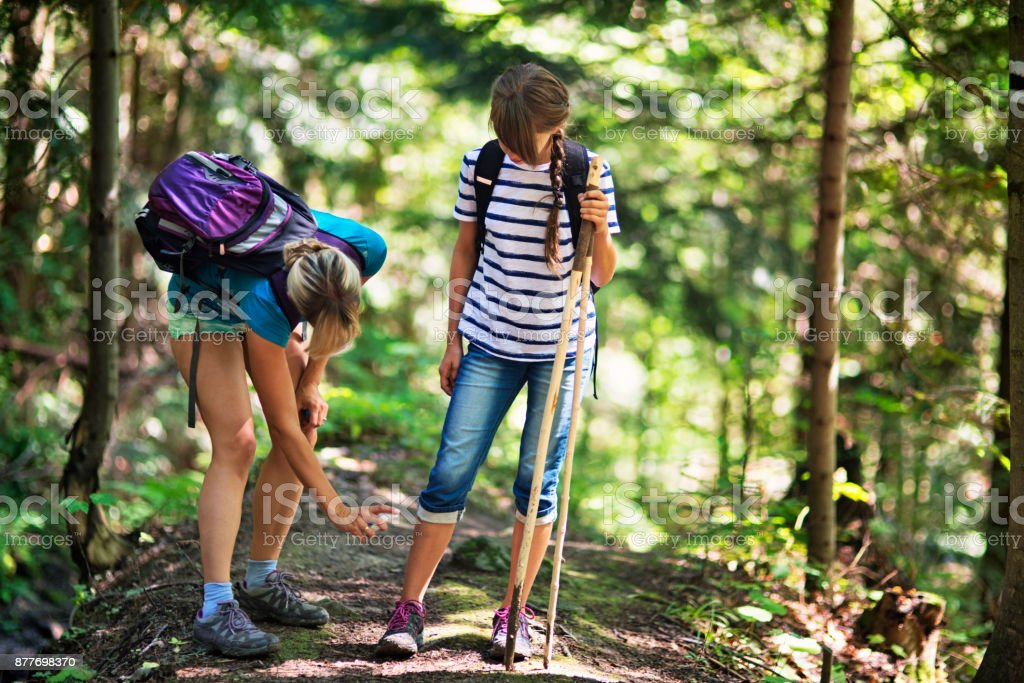 Mother applying tick repellent on daughter stock photo