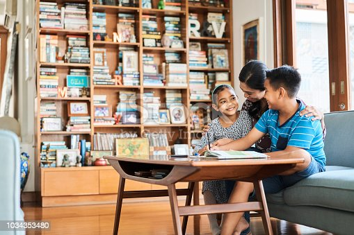 istock Mother assisting children in studies at home 1034353480