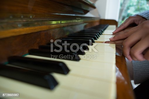 istock Mother assisting daughter in playing piano at home 872865582