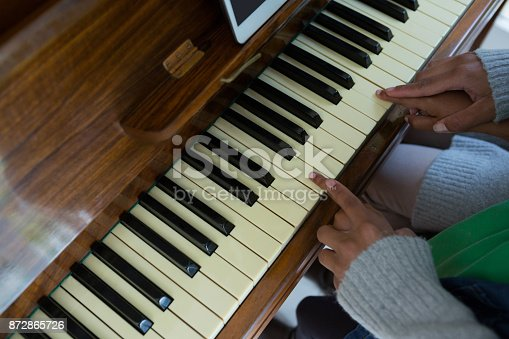 istock Mother assisting daughter in playing piano at home 872865726