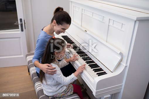istock Mother assisting daughter in playing piano 869795916